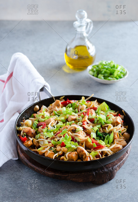 Chicken stir fry with bell peppers, bean sprouts and bok choy in frying pan