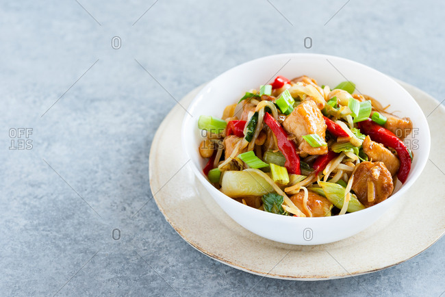 Close up of chicken stir fry with bell peppers, bean sprouts and bok choy in a bowl