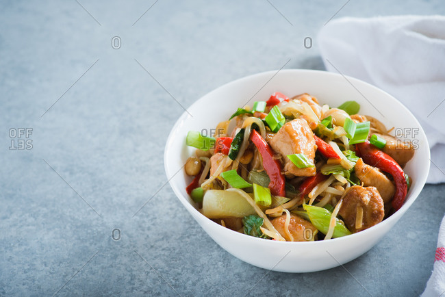 Serving of chicken stir fry with bell peppers, bean sprouts and bok choy in a bowl