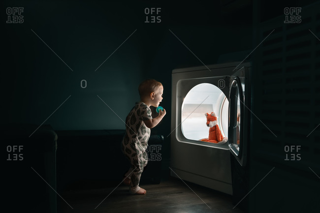 Toddler boy finds his stuffed toy fox in the illuminated dryer at night