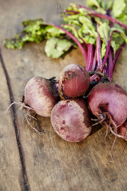 Close up of a bunch of beetroot on a rustic wooden surface