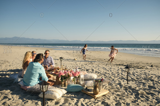 Mature male and female friends enjoying picnic while girls playing at beach against clear sky during sunny day. Riviera Nayarit- Mexico