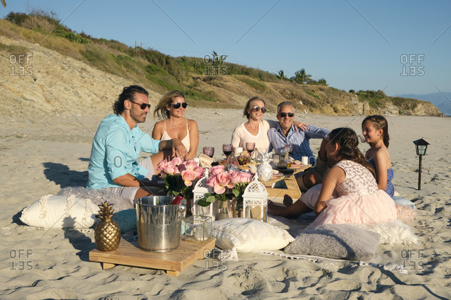 Family and friends enjoying picnic while sitting at beach against blue sky during sunset. Riviera Nayarit- Mexico