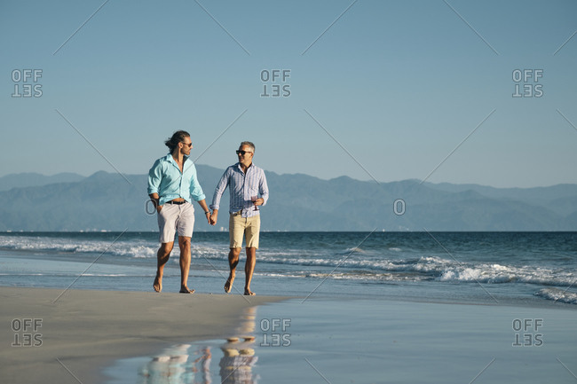 Full length of mature gay men holding hands while walking on shore at beach against clear blue sky- Riviera Nayarit- Mexico