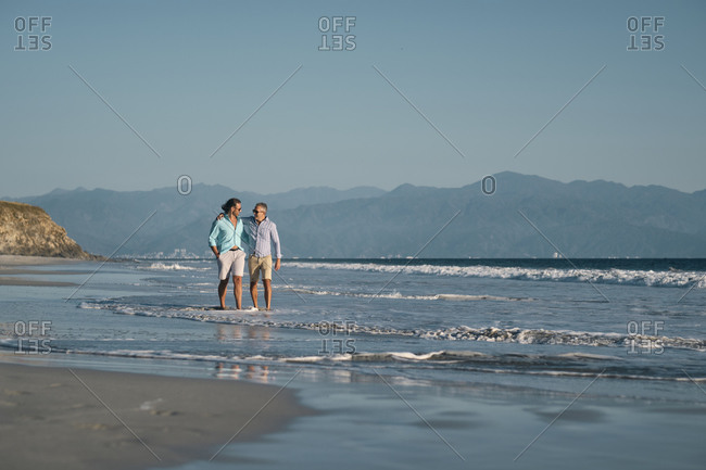 Mature gay men holding hands while walking on shore at beach against clear blue sky- Riviera Nayarit- Mexico