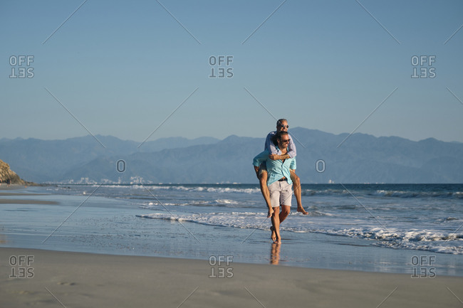 Mature gay man giving piggyback to partner while walking on shore at beach against clear blue sky- Riviera Nayarit- Mexico