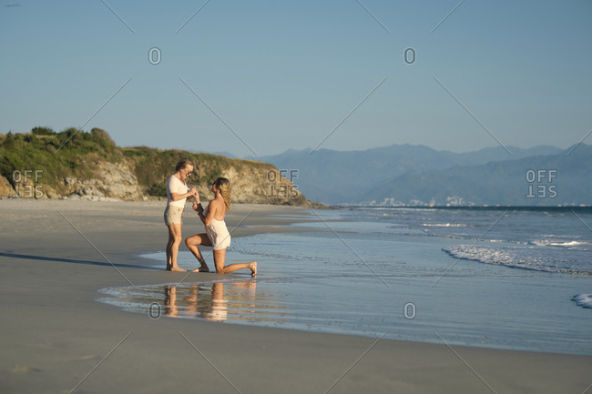 Mature woman proposing lesbian partner at beach against clear blue sky- Riviera Nayarit- Mexico