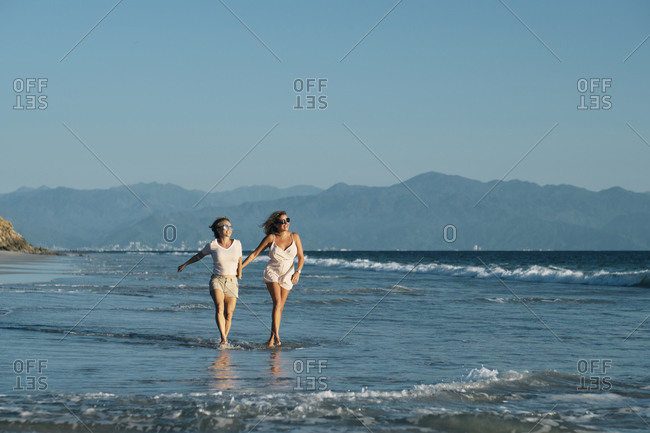Full length of carefree mature lesbians walking on shore at beach against clear blue sky- Riviera Nayarit- Mexico