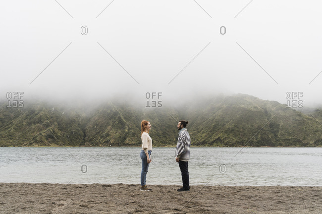 Happy couple standing face to face at lakeshore in Sao Miguel Island- Azores- Portugal