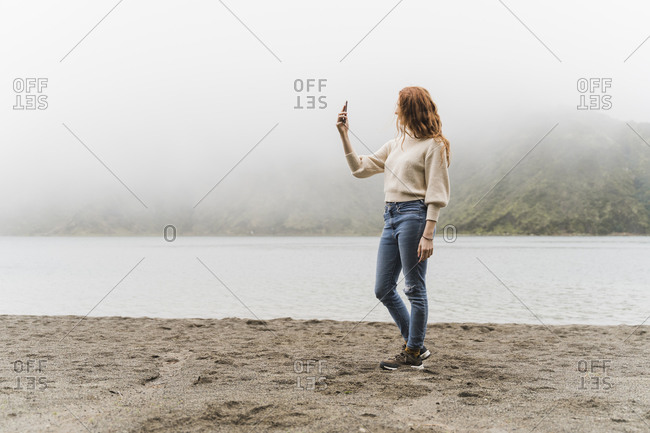 Woman photographing at lakeshore while exploring Sao Miguel Island- Azores- Portugal