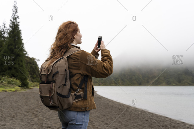 Female explorer carrying backpack while photographing through smart phone at Sao Miguel Island- Azores- Portugal