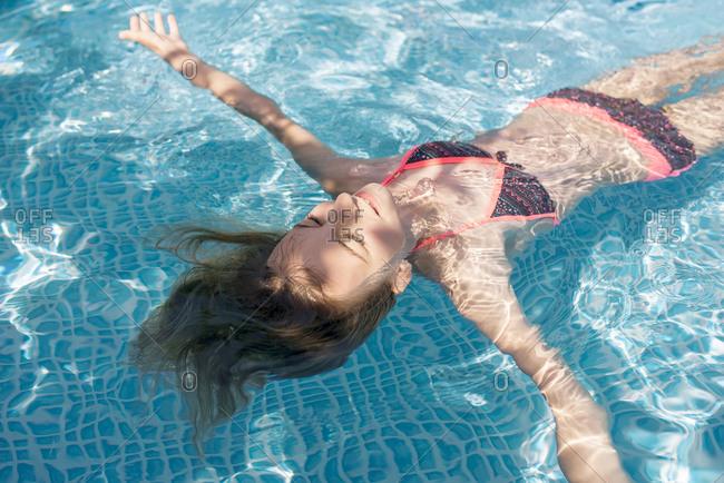 Germany- Brandenburg- Teenage girl floating in pool