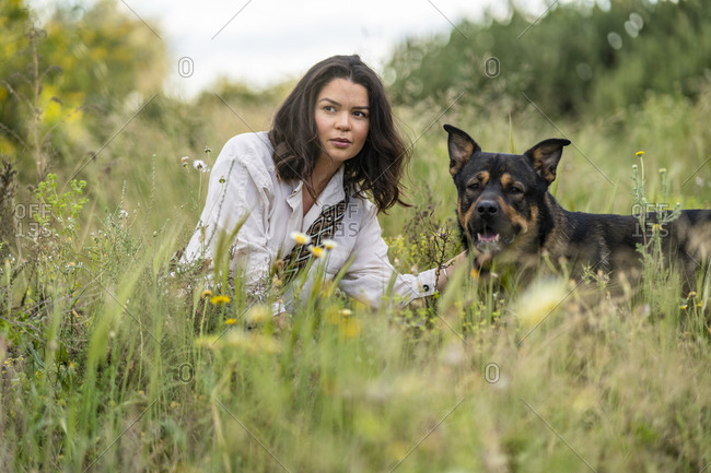 Beautiful young woman crouching by dog while looking away on green plants against sky- Alicante- Alicante Province- Spain