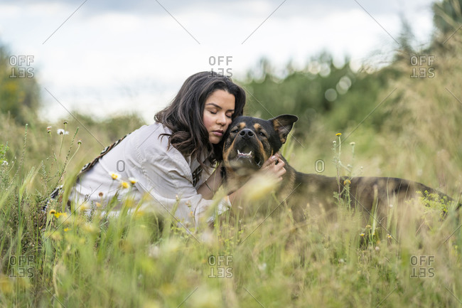Beautiful young woman embracing dog on plants against sky- Alicante- Alicante Province- Spain