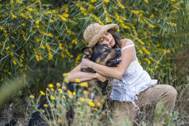 Young woman wearing hat while embracing dog on plants- Alicante- Alicante Province- Spain