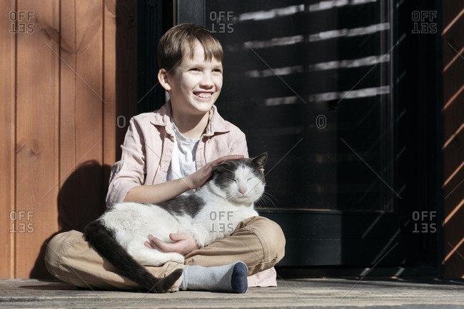 Smiling boy looking away while stroking cat relaxing on him at porch during sunny day- Tarusa- Russia