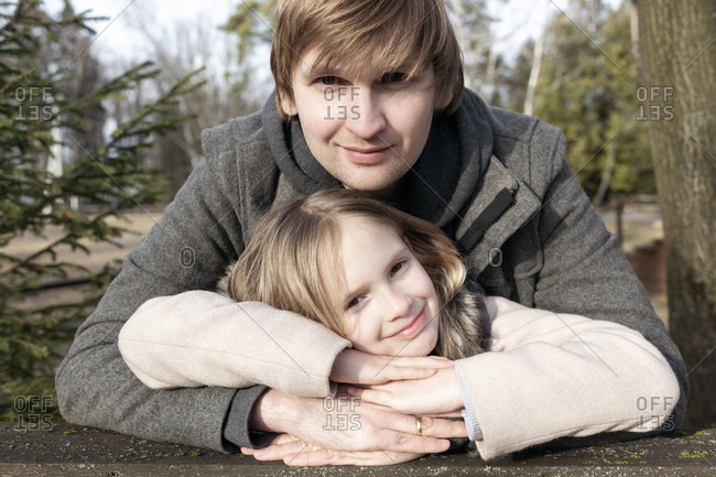Portrait of smiling girl leaning on father's hands at back yard during sunny day- Tarusa- Russia