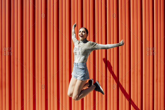 Full length of carefree young woman jumping against red corrugated wall on sunny day