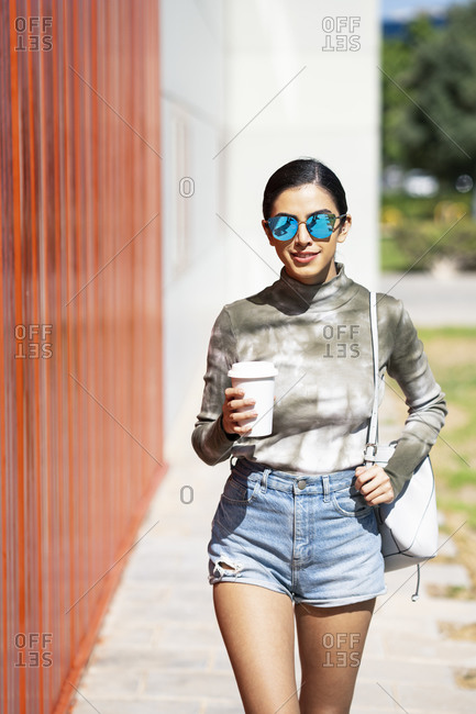 Fashionable young woman holding coffee cup while walking by red corrugated wall on sunny day