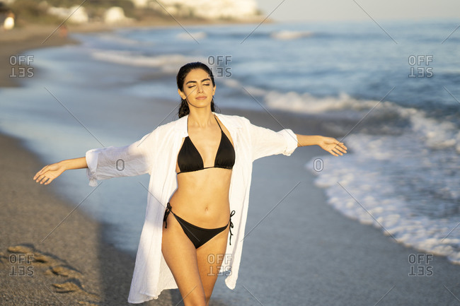 Beautiful young woman enjoying while walking with arms outstretched on shore at beach- Marbella- Andalusia- Spain