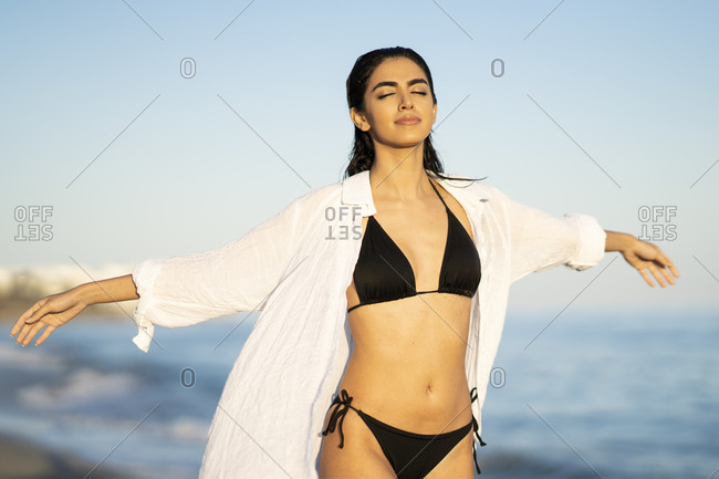 Beautiful young woman walking with arms outstretched and eyes closed at beach against blue sky- Marbella- Andalusia- Spain