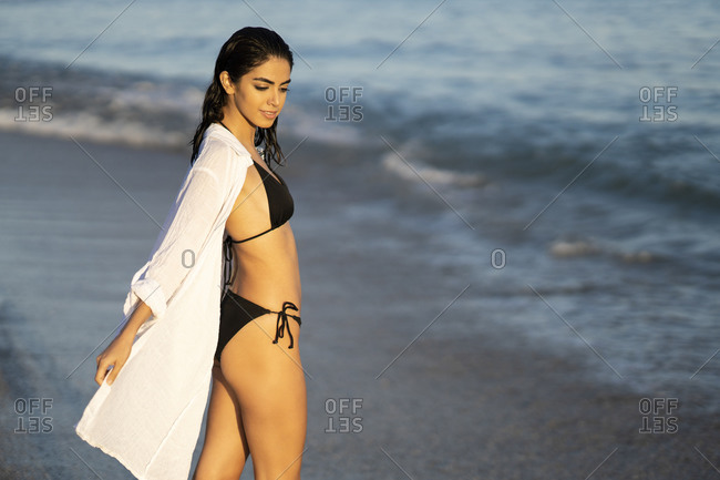 Side view of beautiful young woman enjoying at beach on sunny day- Marbella- Andalusia- Spain