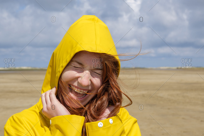 Close-up of carefree redhead teenage girl wearing yellow raincoat while standing at beach against sky on sunny day