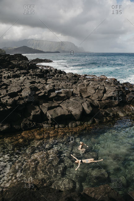 High angle view of friends swimming at Queen's Bath in Kauai- Hawaii Islands- USA