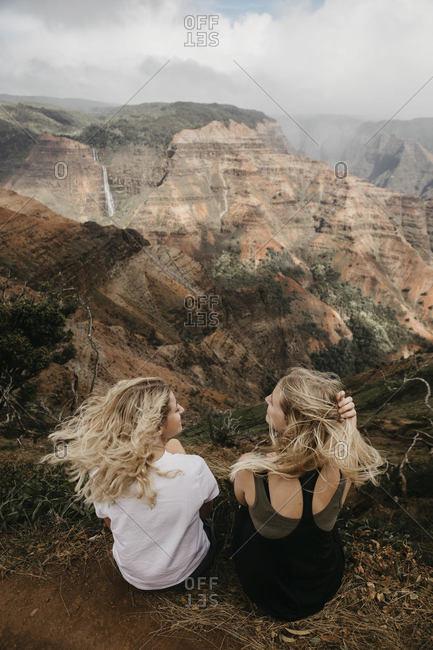 Rear view of friends talking while exploring Waimea Canyon together in Kauai- Hawaii- USA