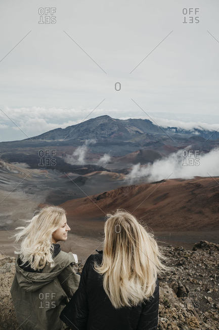 Young friends sitting at Haleakala Crater- Maui- Hawaii- USA