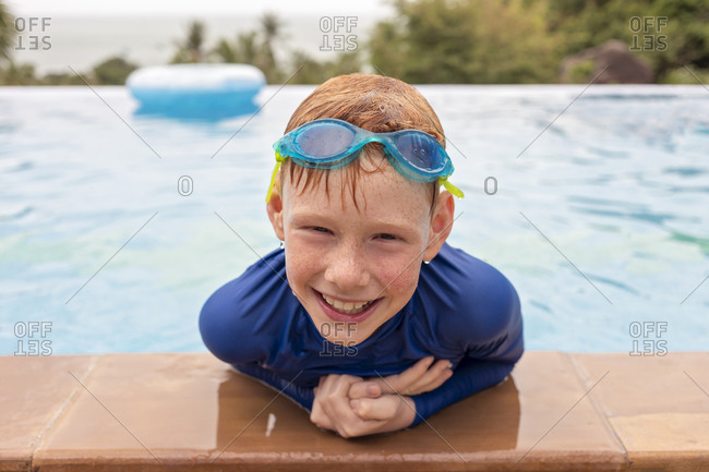 Close-up portrait of smiling boy playing in swimming pool- Thailand- Asia