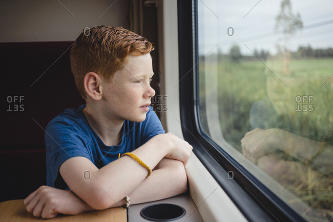 Boy looking through window while traveling in train- Thailand- Asia