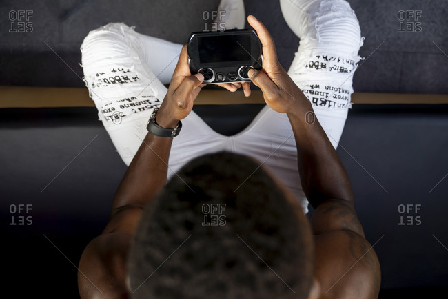 Directly above view of young shirtless man playing handheld video game