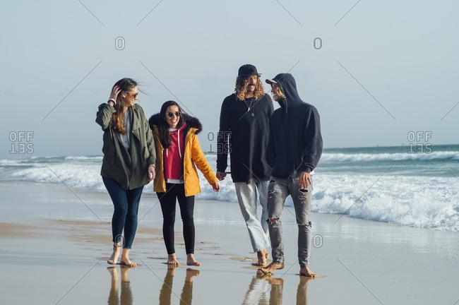 Full length of friends talking while walking on seashore at beach against sky in Tarifa- Spain