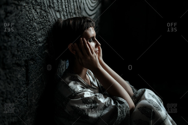 Russia- Moscow- Tired woman with eyes closed and head in hands sitting by wall