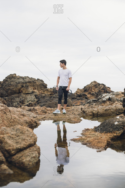Full length of male trail runner standing on rocks with his reflection over water against sky- Ferrol- Galicia- Spain