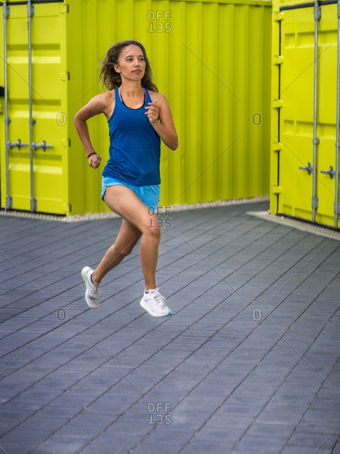 Young woman jogging on pavement in front of cargo containers