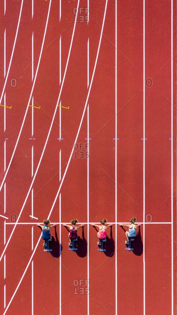 Germany- Baden-Wurttemberg- Winterbach- Aerial view of female sprinters kneeling on starting line