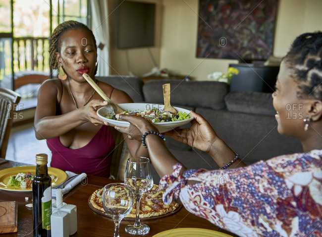 Young woman passing salad plate to female friend sitting at dining table in room