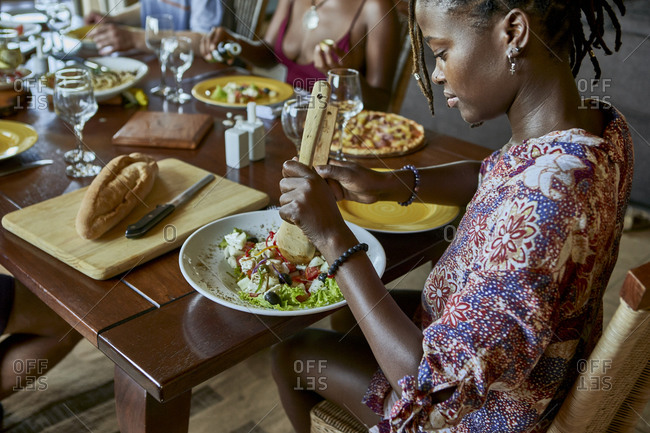 High angle view of young woman serving salad in her plate while sitting at dining table