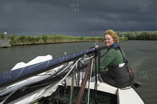 Woman steering sailing boat with lowered mast before crossing bridge, Langweer, Friesland, Netherlands