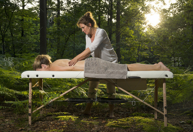 Professional masseuse treats woman on massage table in woods