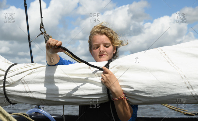 Girl prepares sails on flat-bottom traditional sailing ship, Sneekermeer, Friesland, Netherlands