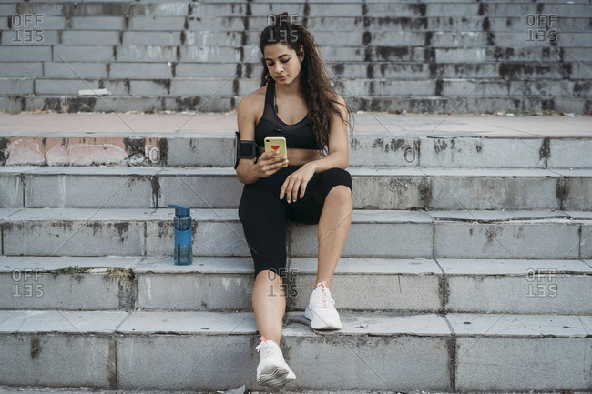 Young woman using smartphone on stairways