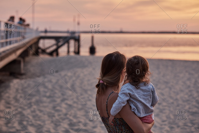 Mother and baby girl enjoying beach at sunset, Arcachon, France