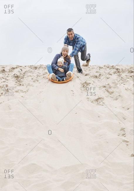 Parents and baby girl sand sledding on dunes