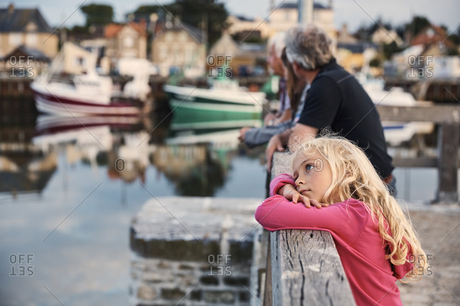 Girl daydreaming by pier, Normandie, France