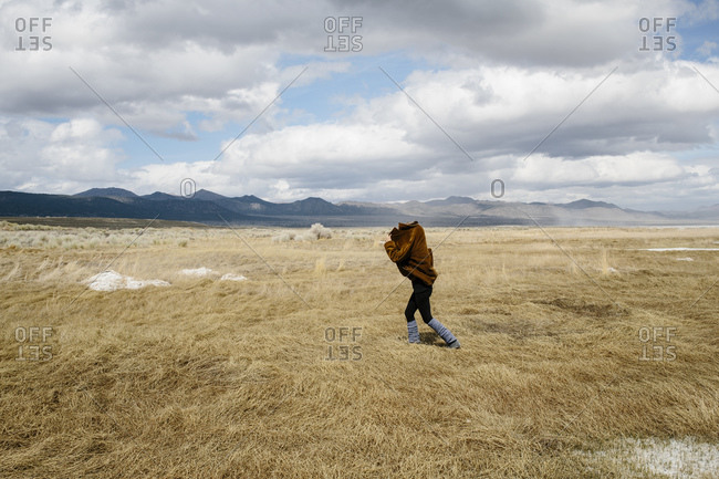 Person walking with jacket over head in countryside, Mammoth, California, USA
