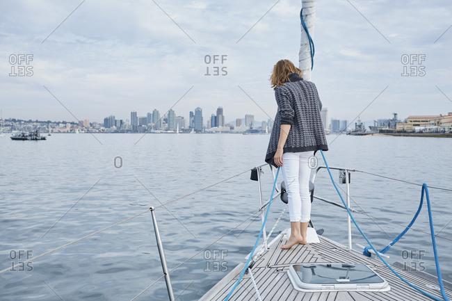 Woman enjoying sea view on bow of sailboat, San Diego, California, USA