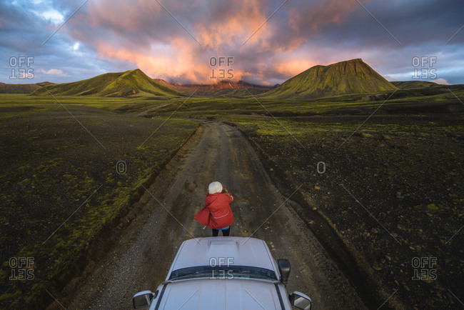 Woman traveler enjoying scenic view of volcanic mountains on vehicle, Landmannalaugar, Highlands, Iceland